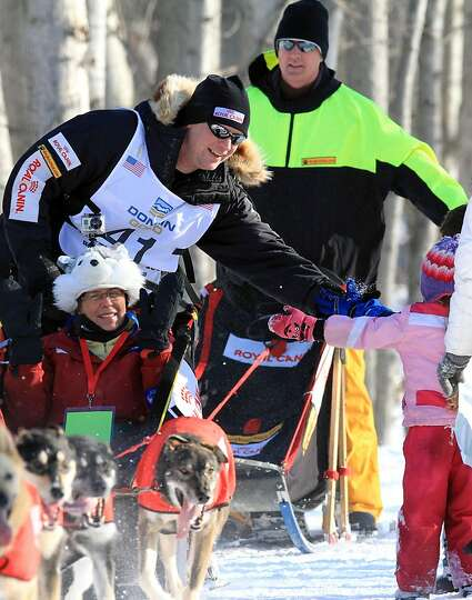 Ed Stielstra greets fans as he drives his team during the ceremonial start of the Iditarod Trail Sle