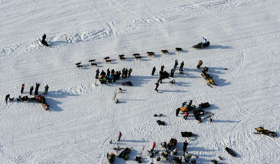 A musher waves to cheering fans gathered on Long Lake during the Iditarod Trail Sled Dog Race, Sunda