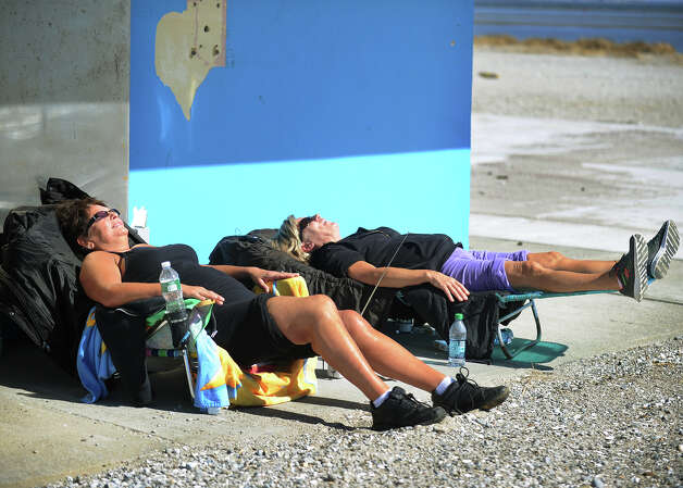 Lisa Treschitta, left, and Gaida Ribas, both of Shelton, catch some rays at Short Beach in Stratford, Conn. on Tuesday, March 5, 2013. The friends said they visit the beach throughout the winter, even removing snow when necessary from their sunbathing spot. Photo: Brian A. Pounds / Connecticut Post