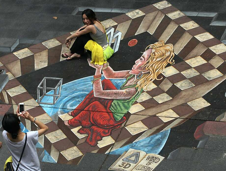 "Best seat in the house:A tourist gets a lift from the subject of the ""World of Illusion,"" a sidewalk painting by Netherlands artist Ruben Poncia during the Living Arts Festival in Bangkok. Photo: Sakchai Lalit, Associated Press"