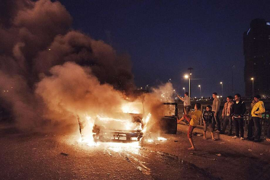 Protesters burn a police cruiser on Cairo's Six of October Bridge during anti-government demonstrations in the Egyptian capital. Photo: Gianluigi Guercia, AFP/Getty Images