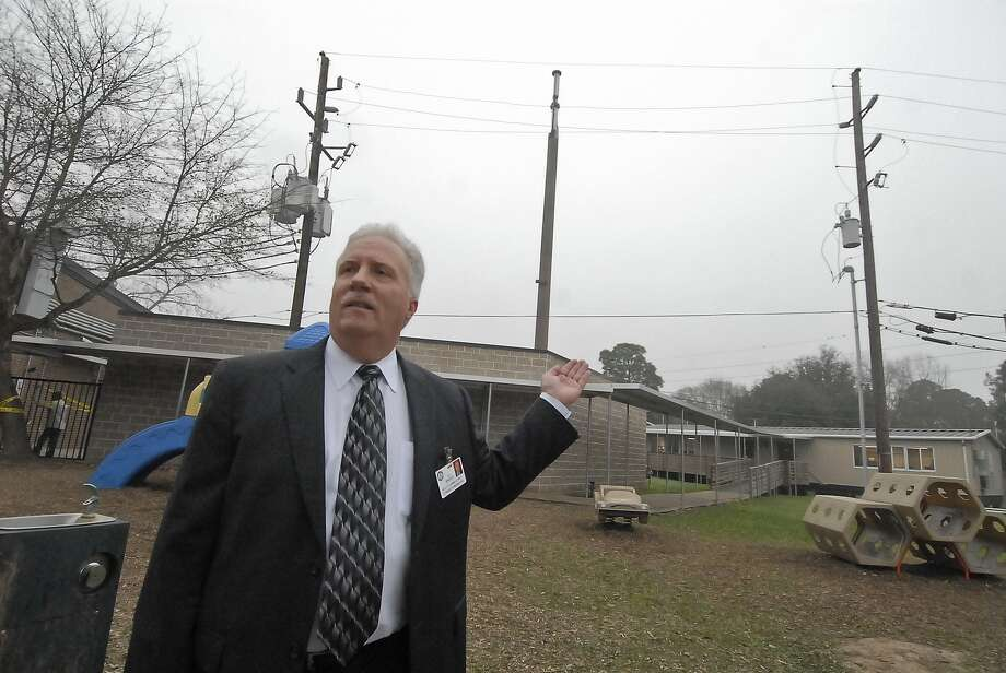 Cy-Fair ISD assistant facilities superintendent Roy Sprague talks about the cell phone tower, between the two power poles behind him, on the campus of Lowry Elementary School. The district is considering camouflaging the tower, after complaints in the area. Photo:  Tony Bullard 2013, Freelance Photographer / © Tony Bullard & the Houston Chronicle