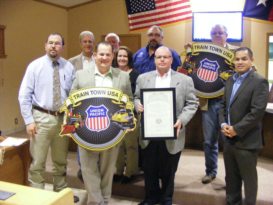 "Kirby Mayor Tim Wilson (front left) holds one of the signs presented to the city Feb. 28, declaring Kirby a ""Train Town USA"" as recognized by the Union Pacific Railroad. Photo: Jeff B. Flinn / NE Herald"