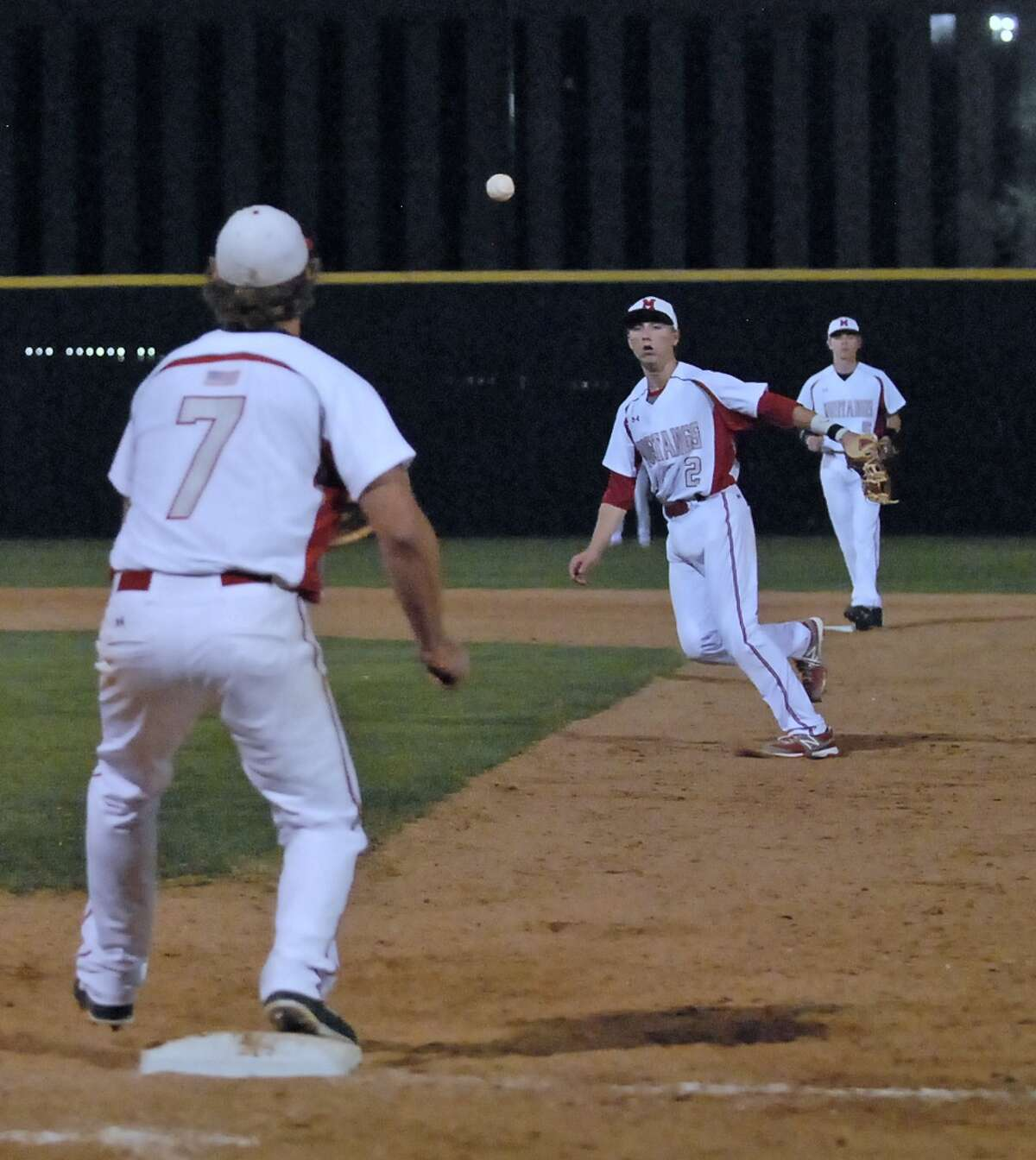 Memorial's Tyler McCloskey (#7) covers first base as Kody Clemens (#2) fields a Stratford hit and throws to first for the force out during their game at Memorial High School Tuesday 2/26/13. Standing on second base is Reid Nagle (#5). Photo by Tony Bullard.