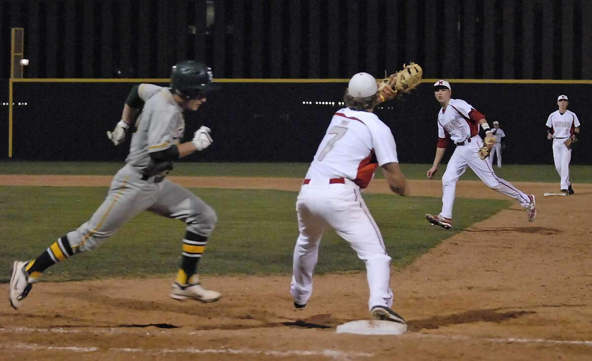 Memorial's Tyler McCloskey (#7) covers first base as Kody Clemens (#2) fields a hit and throws to first to force Stratford's Landon Neumann (#10) out during their game at Memorial High School Tuesday 2/26/13. Photo by Tony Bullard.