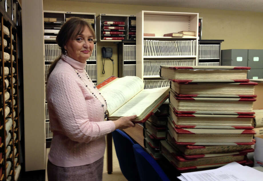 Monroe Town Clerk Marsha Beno holds one of the  town's old record books. Her department is running out of space in its vault. With a grant from the Connecticut State Library's Connecticut Document Preservation Program, the Monroe Town Clerk is having these weighty volumes copied and rebound to take up about 33 percent less space, giving her department more storage space and patrons more elbow room to work. Photo: MariAn Gail Brown