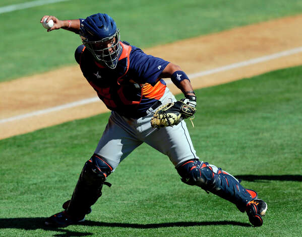 Astros catcher Carlos Corporan throws to first after fielding a bunt attempt by Danny Espinosa of the Nationals during the fifth inning. Photo: David J. Phillip