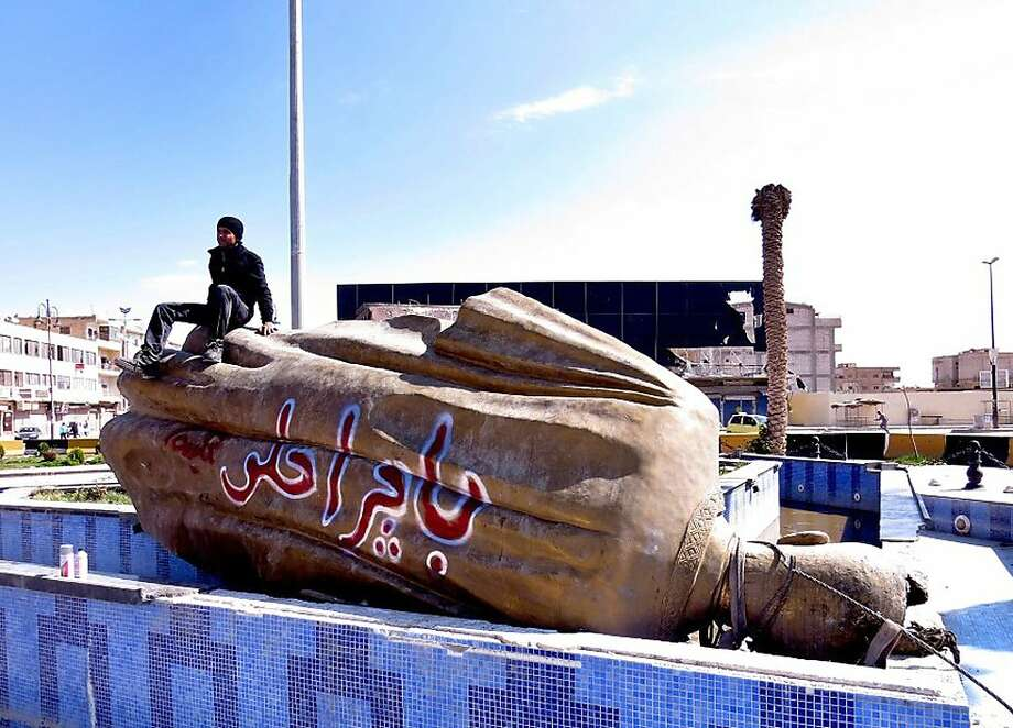 "A man sits on a statue of former Syrian President Hafez Assad after it was dragged down by government opponents in Raqqa and defaced with graffiti reading, ""Tomorrow will be better."" Photo: Anonymous, Associated Press"