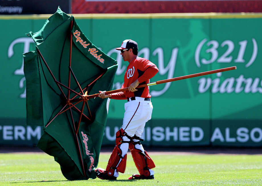 Nationals bullpen catcher Octavio Martinez removes an umbrella which blew onto the field during the second inning. Photo: David J. Phillip