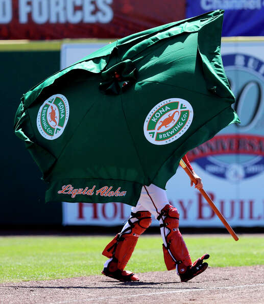 Nationals bullpen catcher Octavio Martinez carries off a rogue umbrella.