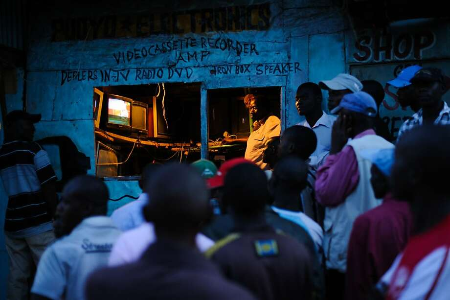 Men watch the incoming provisional election results on a television outside a shop in the Kibera slum of Nairobi, Kenya's capital, March 5, 2013. Kenya's deputy prime minister Uhuru Kenyatta, who faces an international crimes against humanity trial, took an initial lead in presidential elections today, the first since disputed polls five years ago sparked a wave of violence.  Photo: Phil Moore, AFP/Getty Images