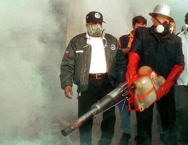 Venezuelan President Hugo Chavez, right, carries a portable fumigation machine used to kill mosquitos that cause dengue fever in the streets of a heavily populated neighborhood of Caracas in 2001. Photo: STR, AFP/Getty Images / AFP