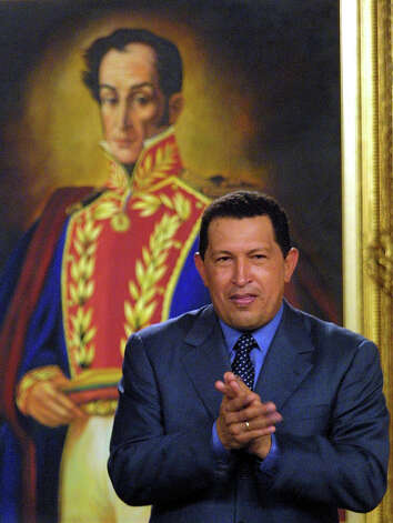 Hugo Chavez, president of Venezuela, stands in front of a painting of Simon Bolivar, as he applauds during a meeting in the Presidential Palace in Caracas, Venezuela 28 June, 2001. Photo: JUAN BARRETO, AFP/Getty Images / AFP