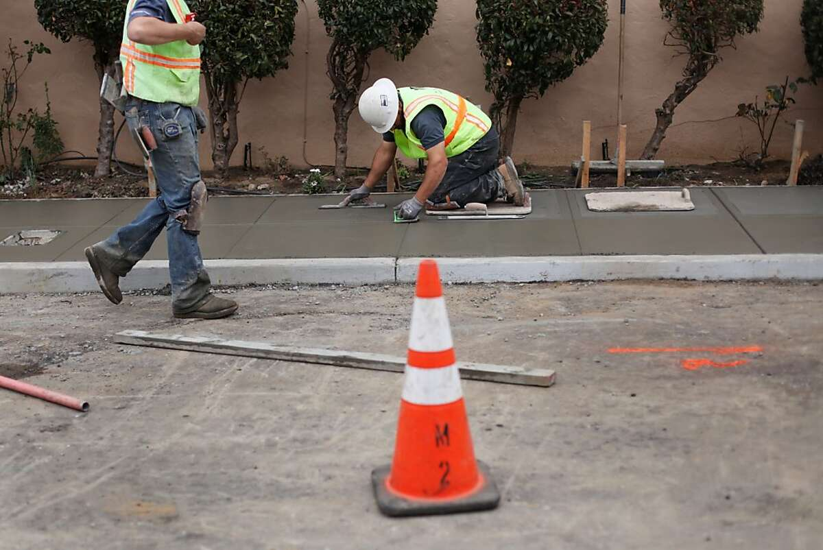 Lino Cevadano, center, works to repair the sidewalk in front of 2700 15th Avenue near Wawona St on March 05, 2013 in the West Portal neighborhood of San Francisco, Calif. The neighborhood is still unstable following a water main break last week, and several houses have been
