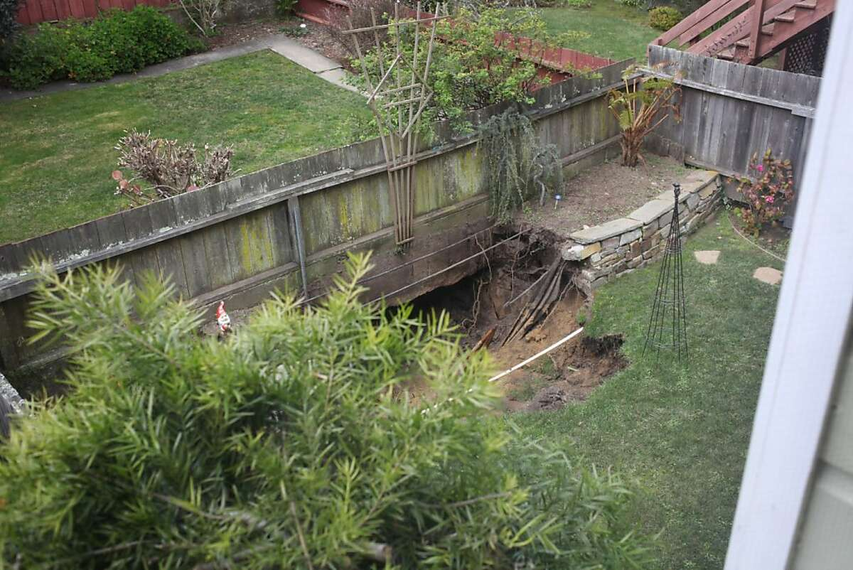 A sinkhole is seen in an adjacent yard from the bedroom window of the Simonian's residence on 15th Avenue near Wawona Street on March 05, 2013 in the West Portal neighborhood of San Francisco, Calif. The neighborhood is still unstable following a water main break last week, and several houses have been