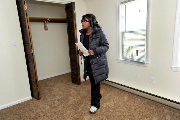 Ranisha Green, 25, looks at the master bedroom in an apartment in Danbury, Conn., that she could possibly rent, Tuesday, March 5, 2013. Photo: Carol Kaliff / The News-Times
