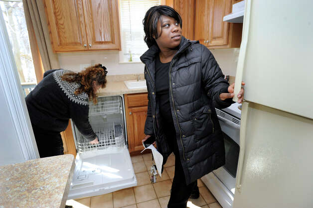 Ranisha Green, 25, right, of Danbury,  looks at the kitchen of an apartment in Danbury, Conn., Tuesday, March 5, 2013. Photo: Carol Kaliff / The News-Times