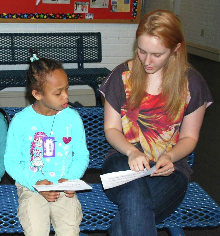 """Girl Scout Gold Award candidate Madeline Wolf, right, shares her passion for singing by bringing Music Theory classes to the Boys and Girls Club. Here she shows Paige Pray how to read music. """"Because I have found so much fulfillment in singing, I just wanted to share information that would help others succeed musically!""""  says Wolf.  Pictured from left to right:  Paige Pray and Madeline Wolf Photo: Contributed Photo"""