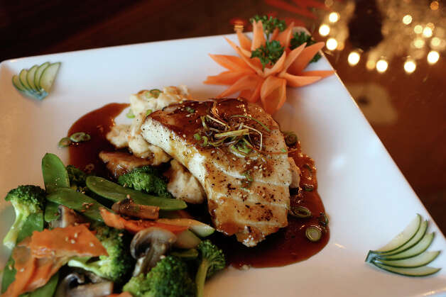 The miso sea bass in garlic ginger sauce is accompanied by mashed potatoes and vegetables. Photo: Lisa Krantz, San Antonio Express-News / San Antonio Express-News