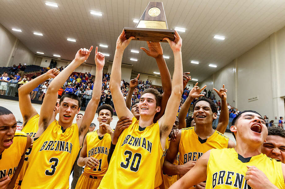 Brennan's Paul Derkowski (left) holds the regional championship trophy as the Bears celebrate their 59-54 overtime victory over Alamo Heights in the boys basketball Region IV-4A final at Littleton Gym on Saturday. Photo: Marvin Pfeiffer / Northwest Weekly