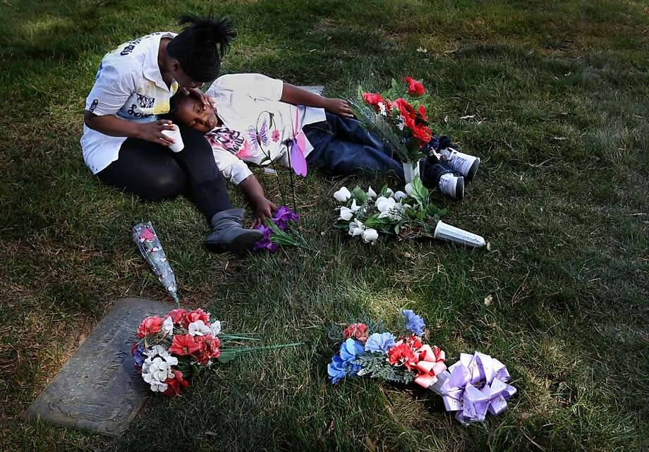 Andrea James comforts her son Andre Landoer, 8, as they sit by the grave of her older son Lamont Price, 17, Saturday, February 16, 2013, at Rolling Hills Memorial Park in Richmond on the one-year anniversary of his murder. Photo: Lacy Atkins, The Chronicle