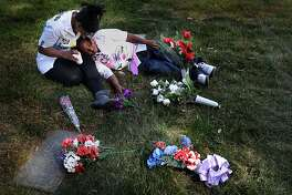 Andrea James comforts her son Andre Landoer , 8, as she sits at the graveside of her son Lamont Price, 17, Saturday, February 16, 2013, in Rolling Hills Memorial Park in Richmond, Calif. on the one-year anniversary of his murder.