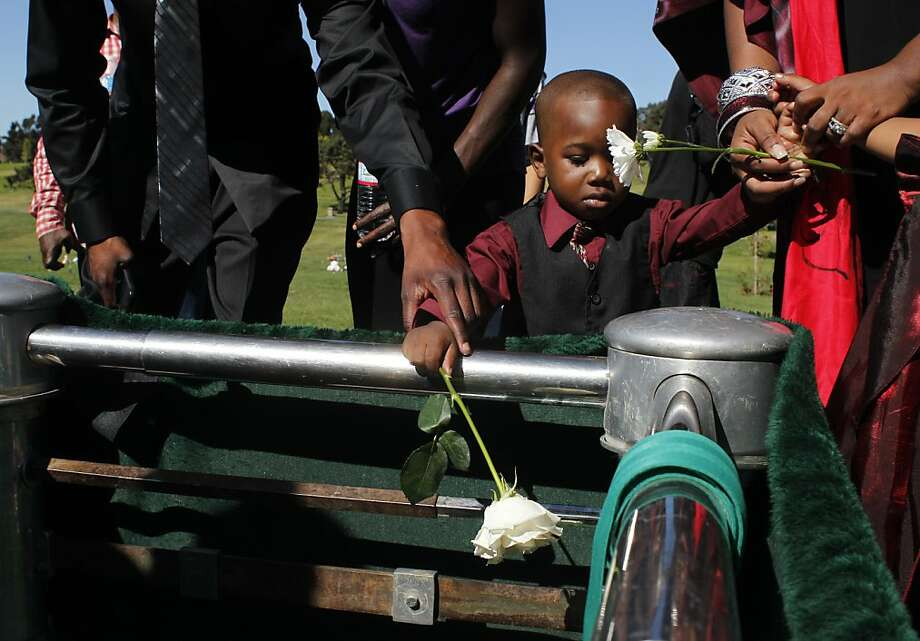 Kawshir Corbray drops a flower into the grave of his stepbrother Angelo Price Corbray on October 16, 2012 at Rolling Hills Memorial Park in Richmond. Photo: Lacy Atkins, The Chronicle