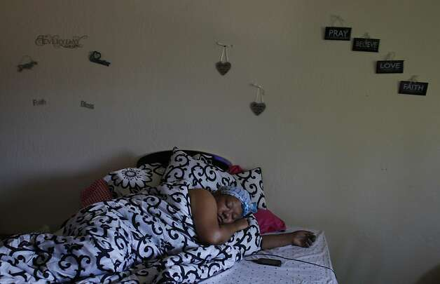 LaTanya Lozano lies in bed while she grieves the murder of her son Shonte Maurice-Corey Daniels, Jr., 15, on May 8, 2012, in her Hayward apartment. Her cell phone received constant text messages and phone calls from friends and family checking on her well-being. She lost another son, Rashad Akeem Meredith, 20, five months later. He was also shot and killed in Oakland. Photo: Lacy Atkins, The Chronicle