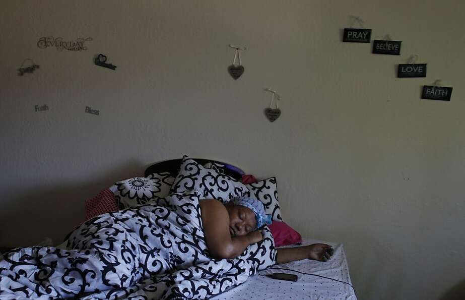 LaTanya Lozano lies in bed while she grieves the murder of her son Shonte Maurice-Corey Daniels, Jr.