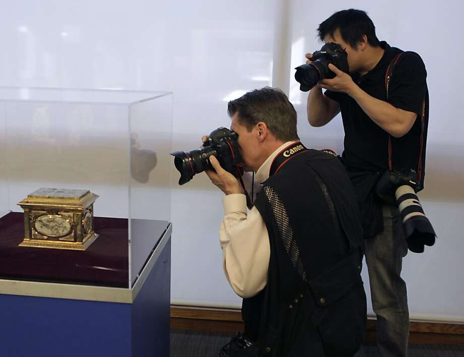 News photographers shoot a gold-and-quartz jewelry box worth $805,000 that was stolen in January from the Oakland Museum of California, recovered and is displayed in a guarded case. Photo: Paul Chinn, The Chronicle