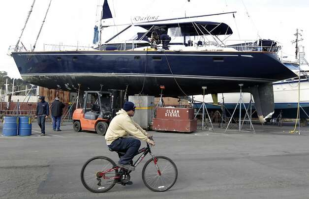 A boatyard worker rides past the Darling at Bay Marine Boatworks in Richmond, Calif. on Tuesday, March 5, 2013. Three people remain in custody after they reportedly stole the 82' vessel from a marina in Sausalito and ran the boat aground in Pacifica early Monday morning. Photo: Paul Chinn, The Chronicle