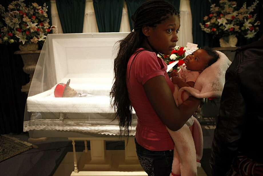 Tajjeunna Price, sister of Lamont Price, holds his five-week-old daughter KaMaya during the family viewing of his body at Whitted-Atkins Funeral Home, Wednesday Feb. 28, 2012, in Oakland. Lamont, 17, was one of the 131 killed in Oakland  2012. Photo: Lacy Atkins, The Chronicle