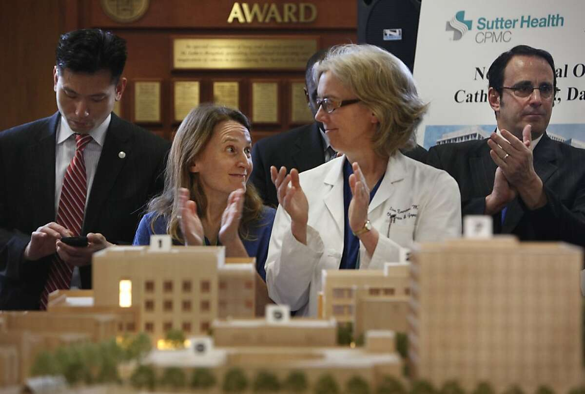 Dr. Karen Makely (second from left) and Dr. Lisa Everson (second from right) applaud speakers during a press conference at St. Lukes Hospital announcing plans to rebuild California Pacific Medical Center's healthcare facilities on Tuesday, March 5, 2013 in San Francisco, Calif.