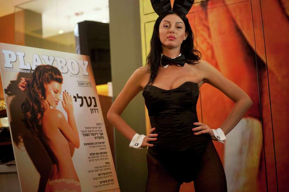 "A model dressed as a Playboy bunny poses with the first Hebrew language edition of the popular men's magazine in Tel Aviv, Israel, Tuesday, March 5, 2013. Israelis can now read Playboy ""for the articles."" A U.S. emigre, Daniel Pomerantz, on Tuesday launched the first Hebrew language edition of the popular men's magazine. Playboy has been widely available in Israel for years, but this marks the first local edition of the magazine. It features Israeli models and articles by Israeli writers. It's not clear how well the magazine will be received in the Holy Land, where religious sensitivities simmer under the surface and observant Jews and Muslims live by strict modesty rules. Adult magazines and videos are freely available, but not with local models and not in Hebrew. Playboy was launched in 1953 with the iconic Marilyn Monroe centerfold. It peaked in popularity in the 1970's. Circulation has declined since the rise of adult Internet sites. (AP Photo/Ariel Schalit) Photo: Ariel Schalit"