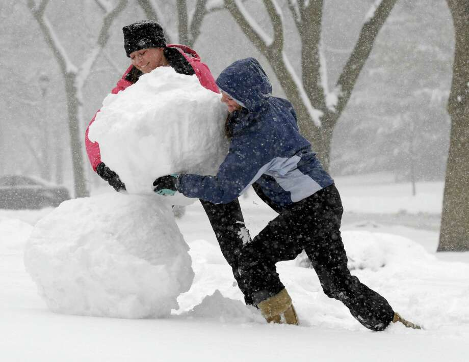 Mary Otto and Maggie Graham build a snowman in Wheaton, Ill., during a snow storm in the suburbs of Chicago, Ill., on Tuesday, March 5, 2013. Photo: Mark Black, Associated Press / Daily Herald