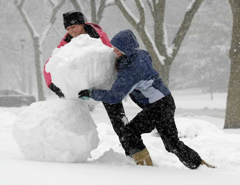 Mary Otto and Maggie Graham build a snowman in Wheaton, Ill., during a snow storm in the suburbs of