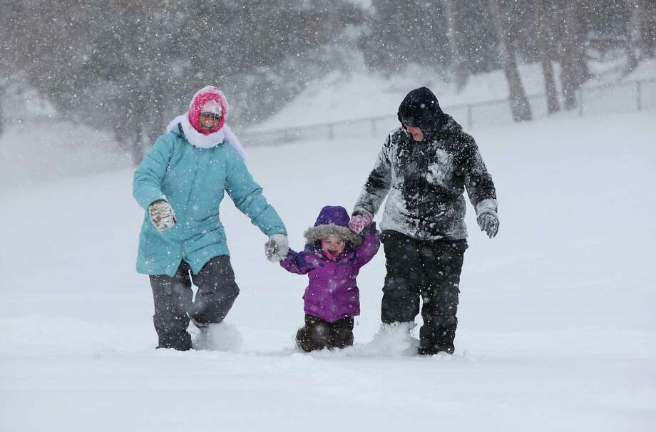 "Maren Piefer, of Fort Lauderdale, Fla., left, enjoys the snow while she visits with her long time friend, Justine Abdelrahmen, of Madison, and her daughter, Aiya, 2, near Cherokee Middle School during a winter storm that came through the area in Madison, Wis., Tuesday, March 5, 2013. ""It's been magical to be here during this time,"" said Peifer, who is from Madison, but moved to Florida to get away from the snow and is now planning on moving back because she misses it. Photo: Amber Arnold, Associated Press / Wisconsin State Journal"
