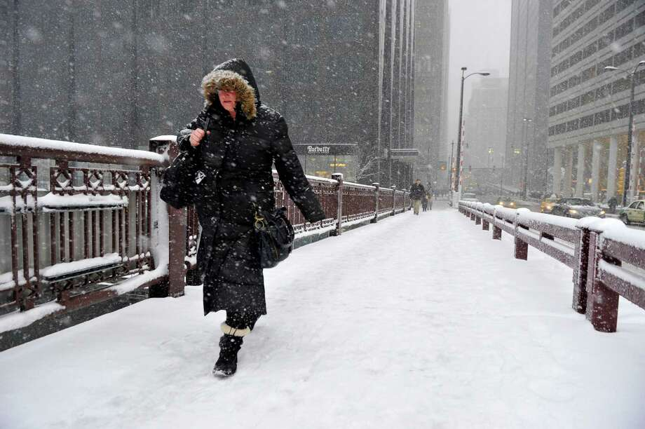 Jennifer Mosby crosses the Adams Street bridge over the Chicago River on March 5, 2013 in Chicago, Illinois. The worst winter storm of the season is expected to dump 7-10 inches of snow on the Chicago area with the worst expected for the evening commute. Photo: Brian Kersey, Getty Images / 2013 Getty Images
