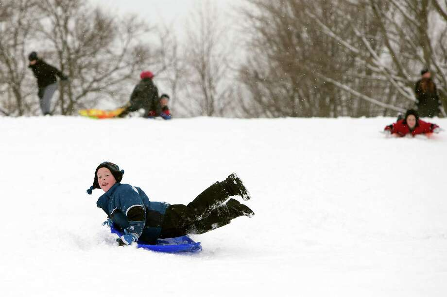 "Max Duesing, 7, of Marion, catches air while sledding at the Chatham Park hill on Tuesday, March 5, 2013, in Marion, Iowa. Snow continued to fall Tuesday morning, with 4-8"" of snow forecast for the Cedar Rapids area. Photo: LIZ MARTIN, Associated Press / THE GAZETTE"