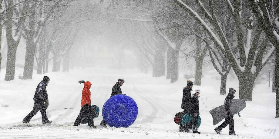 Snow-covered kids head home after a day of sledding in the Chicago suburb of Rolling Meadows, Ill. during a snow storm on Tuesday, March 5, 2013. Photo: Mark Welsh, Associated Press / Daily Herald