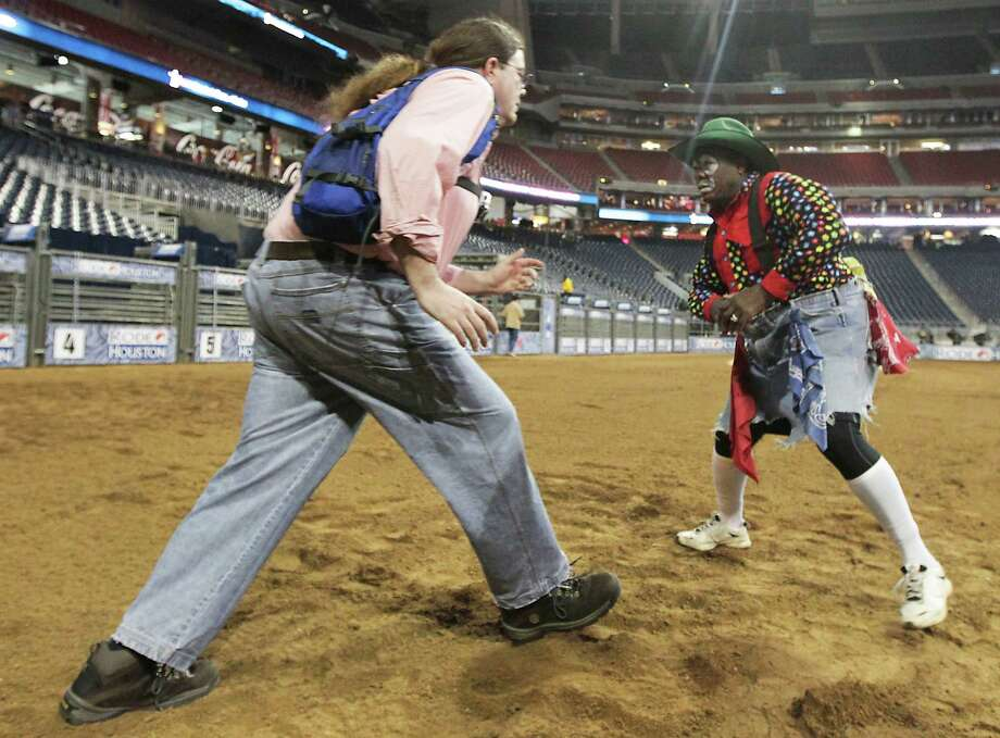 Houston Chronicle reporter Dug Begley, left, and RodeoHouston bullfighter Leon Coffee, right, work on bullfighting techniques at Reliant Stadium Friday, March 1, 2013, in Houston. Photo: James Nielsen, Houston Chronicle / © 2013  Houston Chronicle