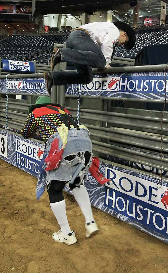 RodeoHouston bullfighters Leon Coffee, left, and Cory Wall, right, demonstrate bullfighting techniques for Houston Chronicle reporter Dug Begley at Reliant Stadium Friday, March 1, 2013, in Houston. Photo: James Nielsen, Houston Chronicle / © 2013  Houston Chronicle