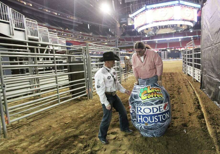 RodeoHouston bullfighters Cory Wall, left, discuss bullfighting techniques as Houston Chronicle reporter Dug Begley stands inside a bullfighting barrel at Reliant Stadium Friday, March 1, 2013, in Houston. Photo: James Nielsen, Houston Chronicle / © 2013  Houston Chronicle