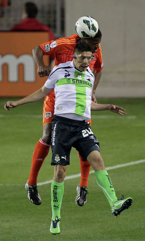 The Dynamo's Boniek Garcia left, heads the ball over Santos Laguna's Oribe Peralta. Photo: James Nielsen, Houston Chronicle / © 2013  Houston Chronicle