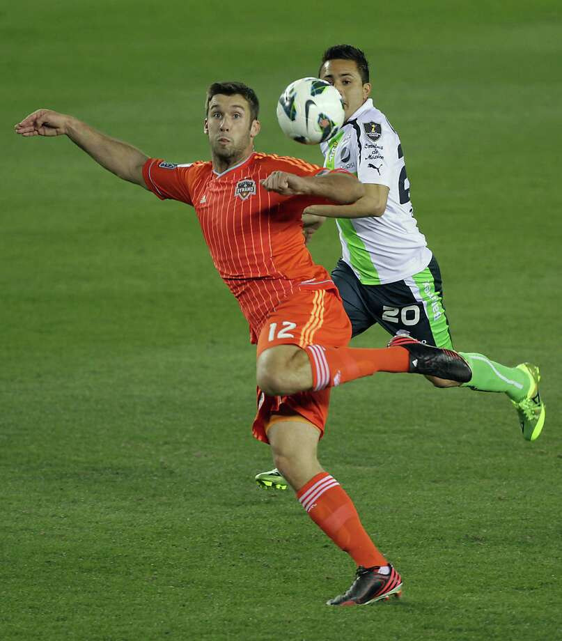 The Dynamo's Will Bruin, left, and Santos Laguna's Omar Mares, right, are focused on the ball. Photo: James Nielsen, Houston Chronicle / © 2013  Houston Chronicle
