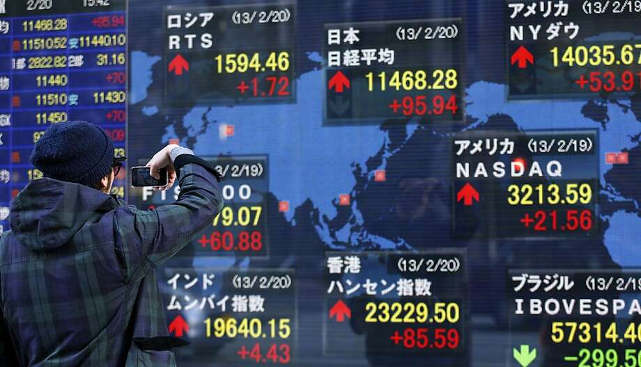 FILE - In this Wednesday, Feb. 20, 2013, file photo, a man takes a photograph of the electronic stock board of a securities firm in Tokyo. U.S. stocks are not alone in racing ahead this year. Many markets in Europe and Asia are trading at multi-year highs, too, in part because of Wall Street's rally. (AP Photo/Shizuo Kambayashi, File) Photo: Shizuo Kambayashi, Associated Press