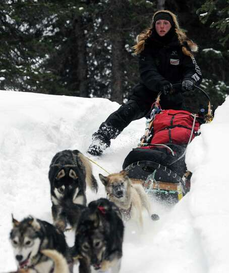 Musher Anna Berington negotiates a steep drop off in the trail after departing the Finger Lake check