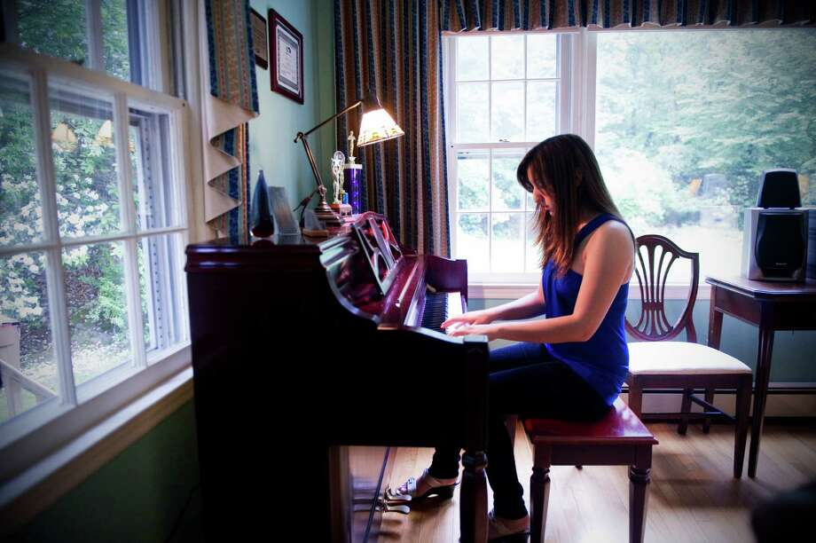 "Musician Lisa Occhino, photographed in 2011 in her home in Stamford, Conn., was recently named the first-place winner in BMI Foundation's 15th annual John Lennon Scholarship songwriting competition for her song ""You Will Never Understand."" She is currently a student at Berklee College of Music in Boston. Photo: Keelin Daly, ST / Stamford Advocate"
