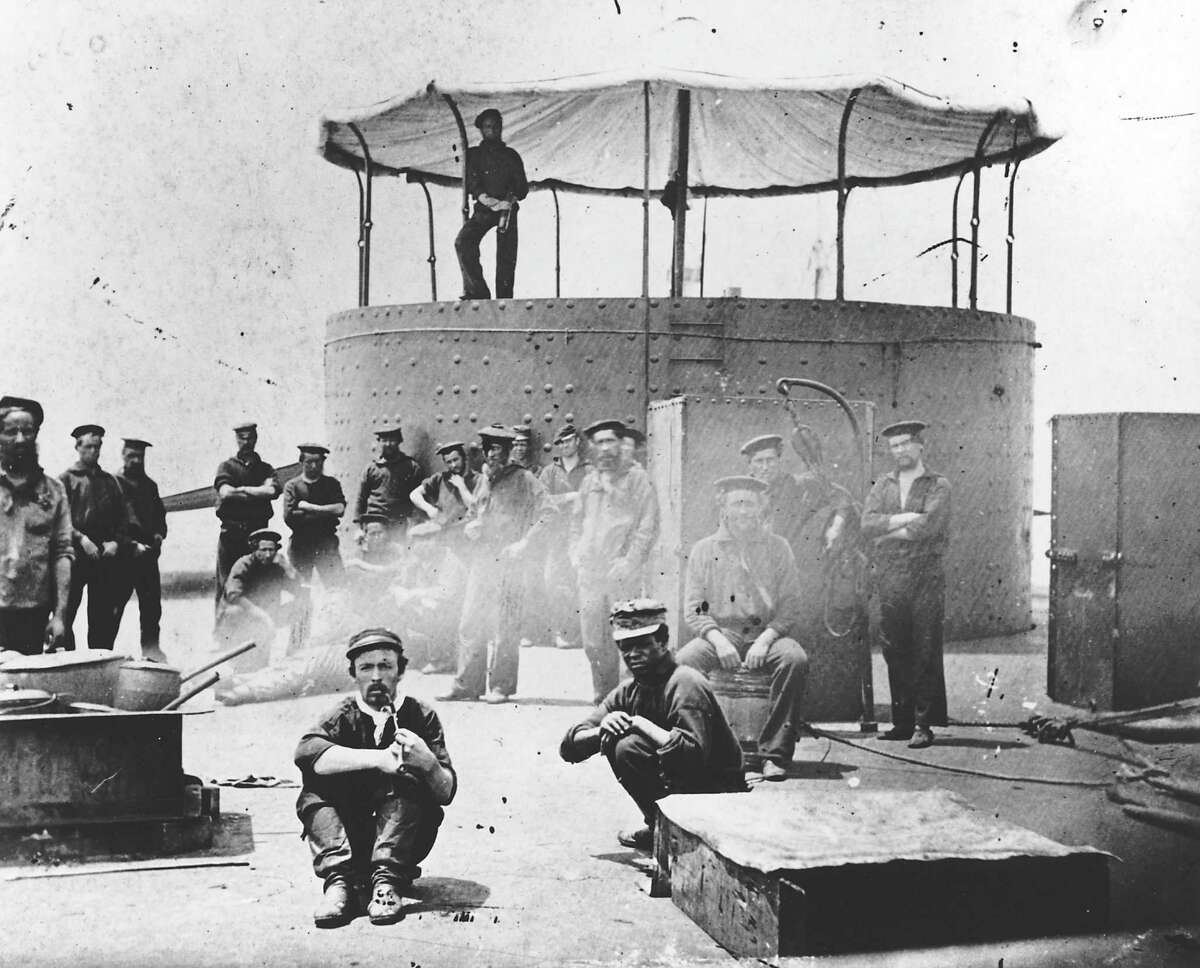 FILE ?-This 1862 photo provided by The Mariners' Museum shows crew sitting on the deck of the Civil War ironclad USS Monitor. Wednesday, March 6, 2013, the remains of two of the 16 crewmen, who died when the Union vessel sank off North Carolina 150 years ago, will be interred at Arlington National Cemetery. They will not lack for mourners as dozens of people with suspected or known family ties to those who died are traveling from around the nation to attend. The revolving gun turret now being conserved at The Mariners' Museum can be seen in the background. (AP Photo/The Mariners' Museum)