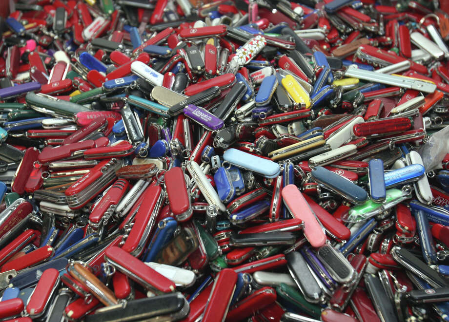 FILE - In this Sept. 26, 2006, file photo, knives of all sizes and types are piled in a box at the State of Georgia Surplus Property Division store in Tucker, Ga., and are just a few of the hundreds of items discarded at the security checkpoints of Hartsfield-Jackson Atlanta International Airport that will be for sale at the store. Airline passengers will be able to carry small knives, souvenir baseball bats, golf clubs and other sports equipment onto planes beginning in April 2013 under a policy change announced Tuesday, March 5, 2013, by the head of the Transportation Security Administration administrator John Pistole. (AP Photo/Gene Blythe, File) Photo: GENE BLYTHE